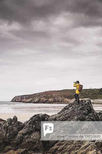 Junge Frau mit gelber Regenjacke am Strand  Blick durch ein Fernglas  Bretagne  Frankreich