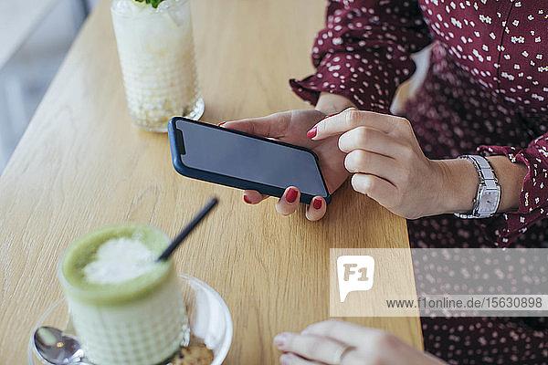 Frau mit Smartphone in der Hand in einem Cafe