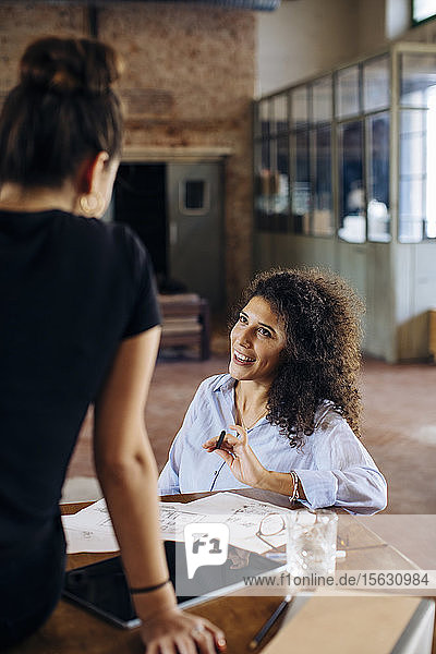 Two young businesswomen talking at table in loft office