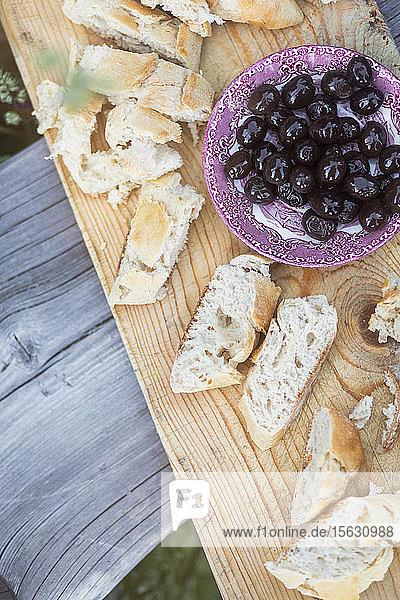 Hochwinkelansicht von Oliven mit Weißbrot auf Holztablett serviert