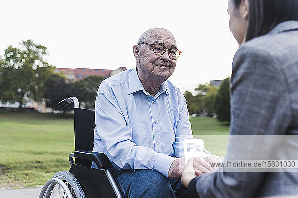Portrait of senior man sitting in wheel chair holding hands with his granddaughter