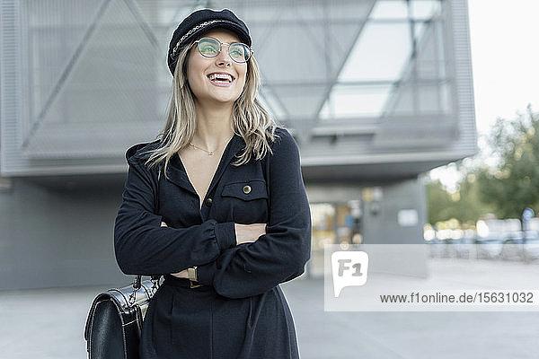 Junge blonde Geschäftsfrau mit schwarzer Matrosenmütze und