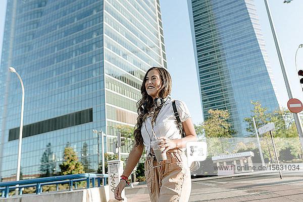 Junge Frau mit Getränk zum Mitnehmen über die Straße  Hochhäuser im Hintergrund