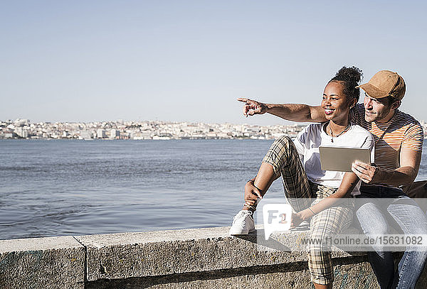 Young couple sitting on a wall at the waterfront with a tablet  Lisbon  Portugal