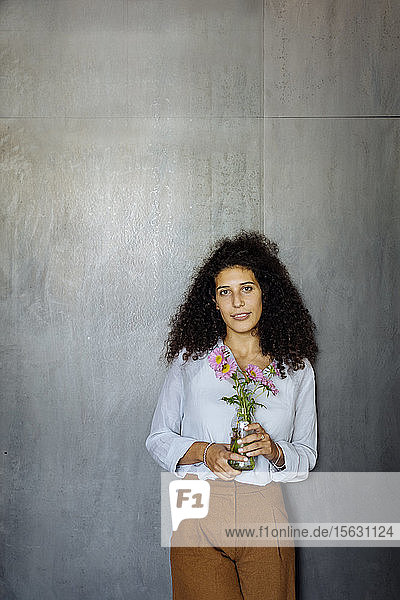 Portrait of a young businesswoman standing in front of a grey wall holding flower vase