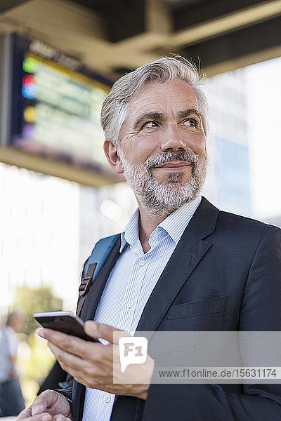 Porträt eines reifen Geschäftsmannes mit Handy am Bahnhof