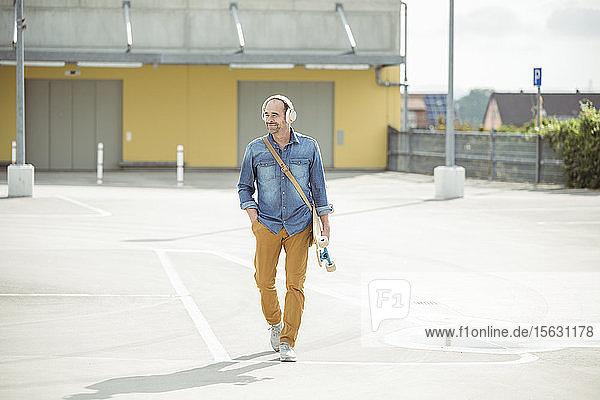 Lässiger reifer Mann mit Kopfhörern und Skateboard auf dem Parkdeck