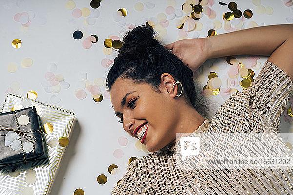 Porträt einer für eine Party gekleideten jungen Frau  die Weihnachten mit Geschenken feiert
