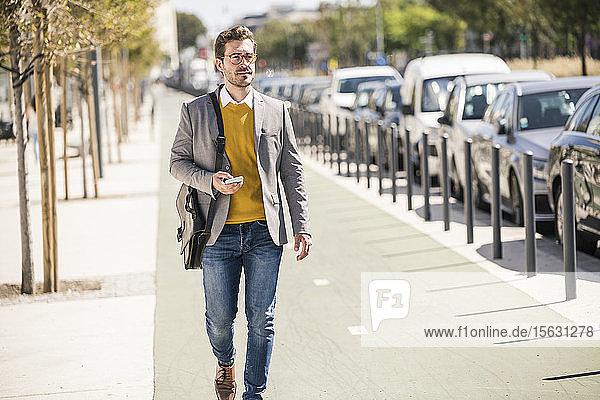 Junger Geschäftsmann in der Stadt unterwegs