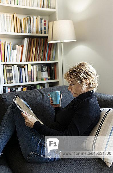 Reife Frau entspannt zu Hause auf der Couch mit Grafiktablett