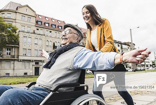 Lachende junge Frau schiebt glücklichen älteren Mann im Rollstuhl