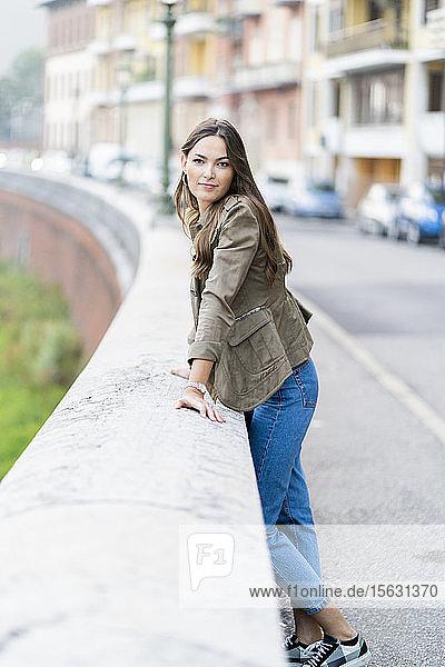 Junge brünette Frau  die in die Kamera schaut und sich an eine Wand lehnt