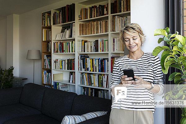 Lächelnde reife Frau  die zu Hause am Fenster im Wohnzimmer steht und ein Smartphone benutzt