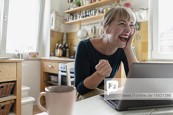 Portrait of woman sitting in the kitchen with laptop crying for joy