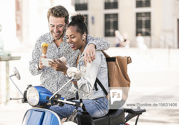 Happy young couple with motor scooter and ice cream using mobile phone in the city  Lisbon  Portugal