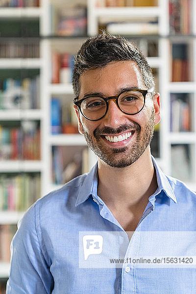 Porträt eines lachenden jungen Mannes mit Brille
