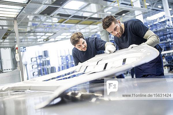 Zwei Kollegen untersuchen Bauteil in Autofabrik