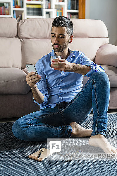 Portrait of young man sitting barefoot on the floor of living room at home looking at smartphone