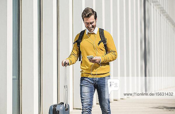 Lächelnder junger Mann mit Rollkoffer und Kopfhörern beim Telefonieren mit dem Handy in der Stadt