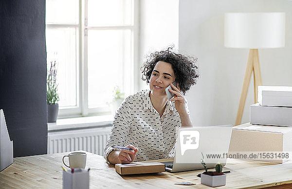 Lächelnde junge Frau am Telefon im Home-Office