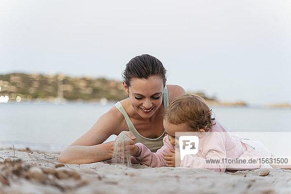 Glückliche Mutter und Tochter spielen mit Sand am Strand