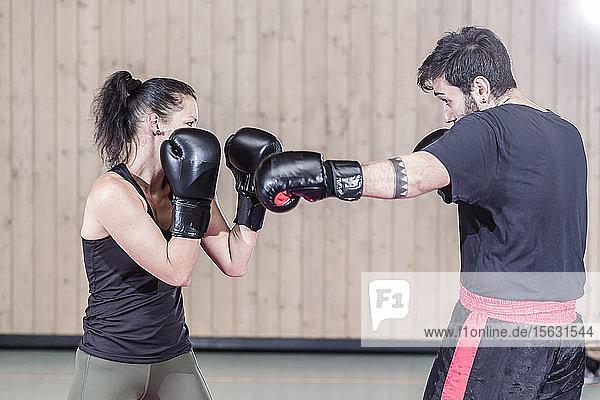Boxerinnen-Sparring mit Trainer in der Sporthalle