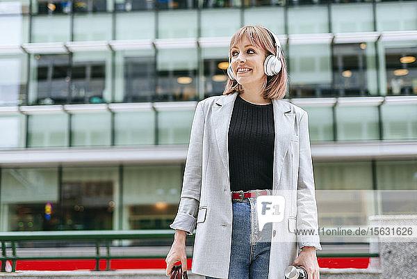 Frau mit Kopfhörern in der Stadt unterwegs