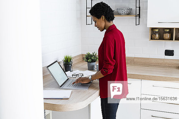 Young woman using laptop in kitchen at home