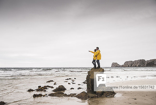 Young woman wearing yellow rain jackets and standing on rock at the beach  Bretagne  France