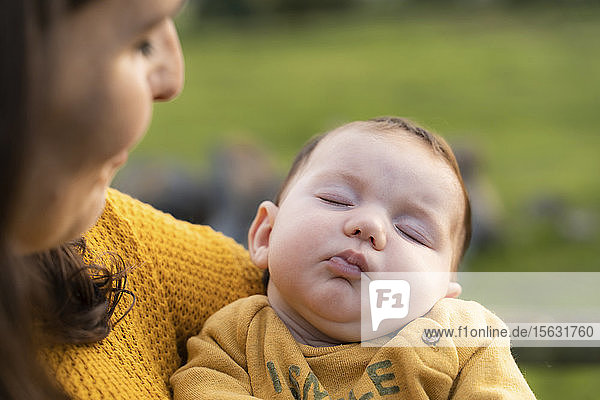 Portrait of baby girl sleeping on her mother's arms