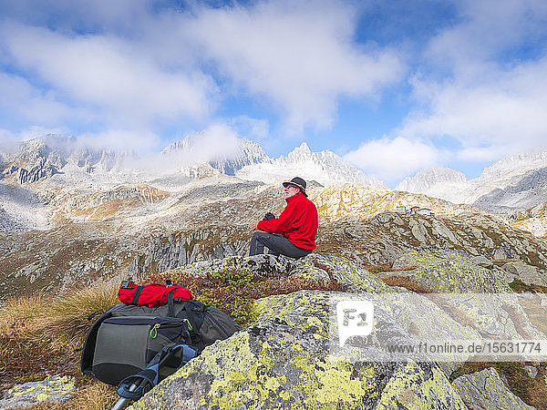 Hiker sitting on a mountain enjoying the view  nature park Adamello  Italy