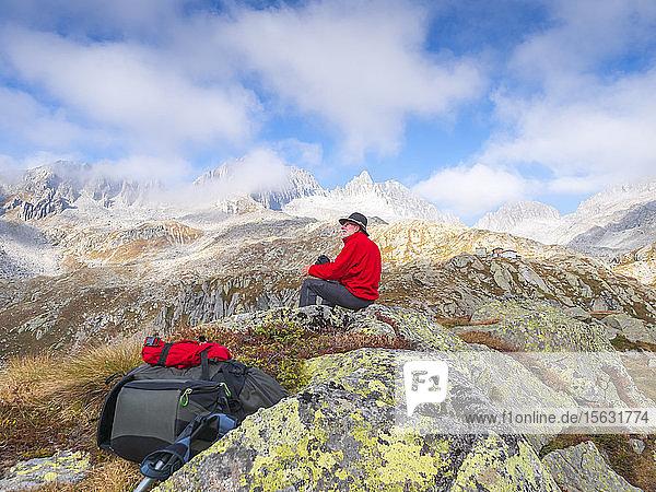 Wanderer sitzt auf einem Berg und geniesst die Aussicht  Naturpark Adamello  Italien