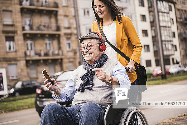 Laughing young woman pushing happy senior man with headphones and smartphone in wheelchair