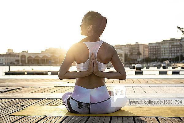 Rückansicht einer asiatischen Frau  die abends auf einem Pier im Hafen Yoga praktiziert Rückansicht einer asiatischen Frau, die abends auf einem Pier im Hafen Yoga praktiziert