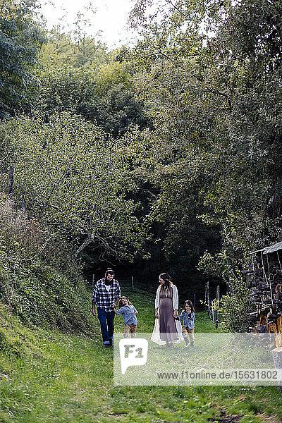 Familie mit zwei Kindern beim Wandern auf dem Land