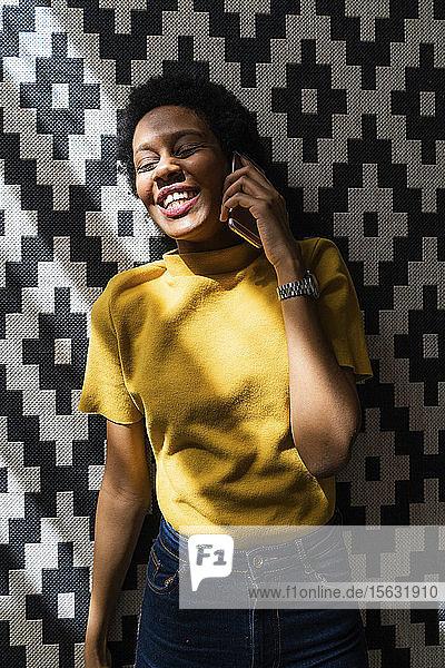Glückliche junge Frau liegt auf Teppich und telefoniert