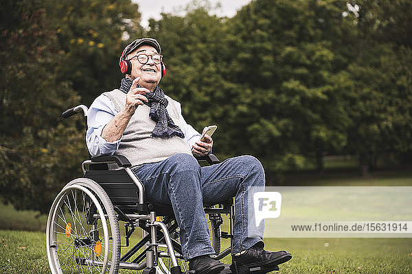 Portrait of happy senior man sitting in wheelchair listening music with smartphone and headphones