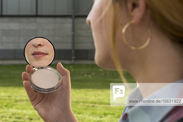 Young woman with nose piercing looking at beauty mirror in her hand