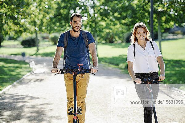 Porträt eines zufriedenen Paares auf Elektrorollern in einem Stadtpark