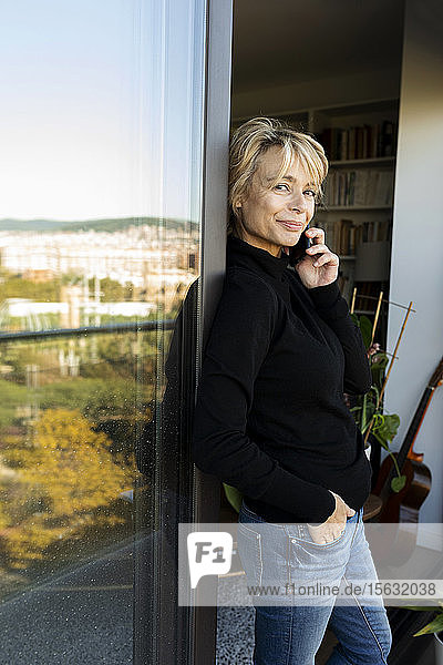 Portrait of mature woman on the phone at the window