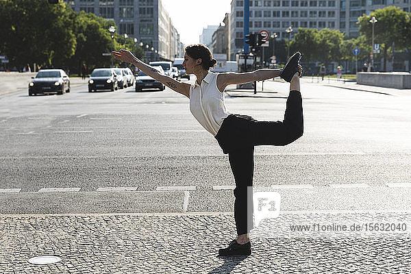 Junge Geschäftsfrau praktiziert Yoga in der Stadt  Berlin  Deutschland