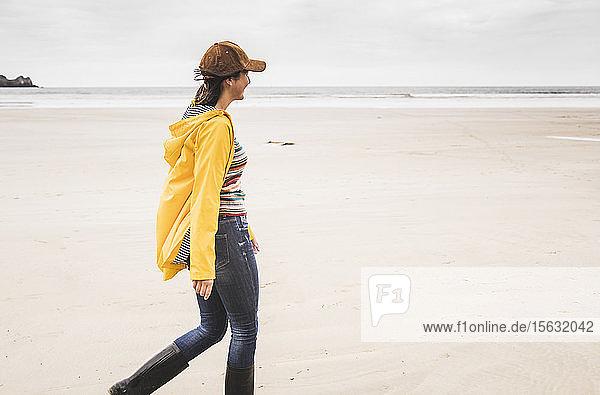 Junge Frau mit gelber Regenjacke am Strand  Bretagne  Frankreich