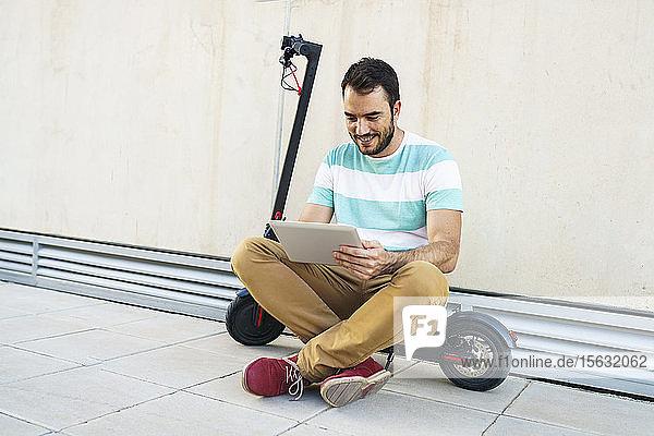 Porträt eines auf einem Elektroroller sitzenden Mannes mit digitalem Tablet