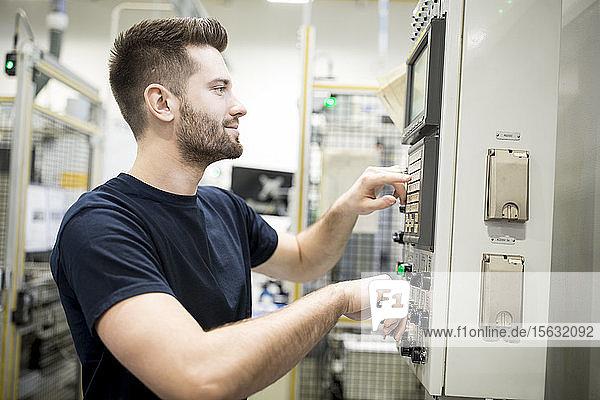 Mann  der in einer modernen Fabrik arbeitet und eine Maschine bedient