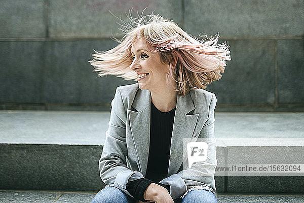 Glückliche Frau bewegt ihr rosa Haar