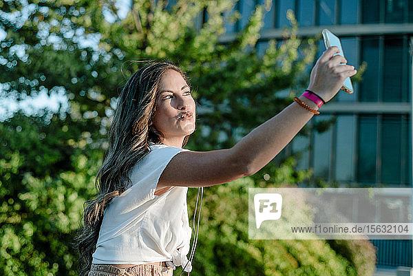 Junge Frau  die mit ihrem Smartphone einen Selfie macht und schmollt
