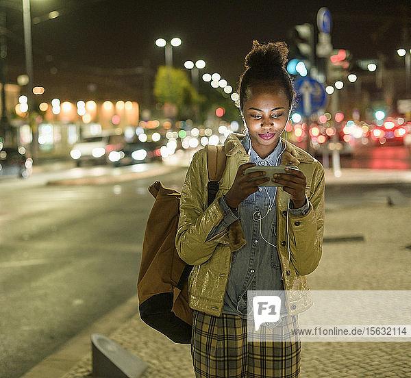 Porträt einer jungen Frau mit Kopfhörer und Smartphone in der Stadt bei Nacht  Lissabon  Portugal