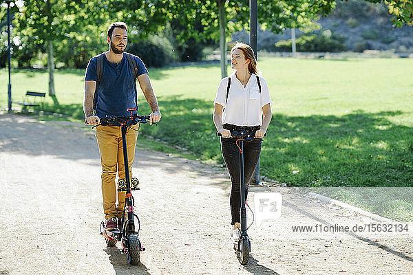Ehepaar fährt Elektroroller in einem Stadtpark