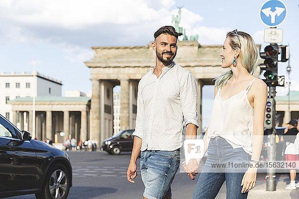 Glückliches junges Paar geht Hand in Hand vor dem Brandenburger Tor  Berlin  Deutschland