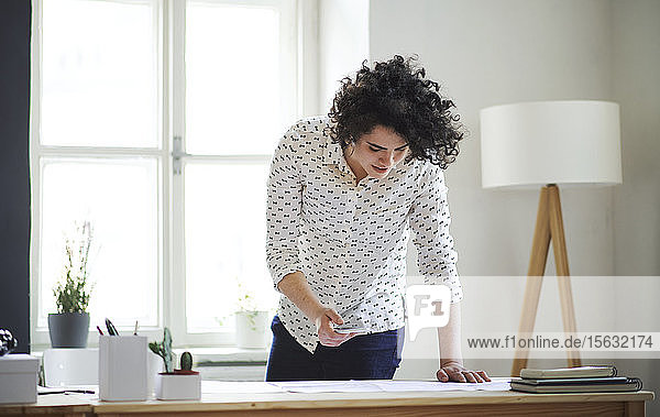 Young woman studying a plan on desk in office